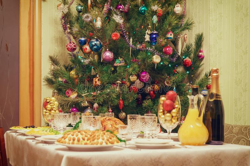 Served table with festive dishes near beautiful decorated Christmas tree in living room interior. Concept of new year holiday at stock image