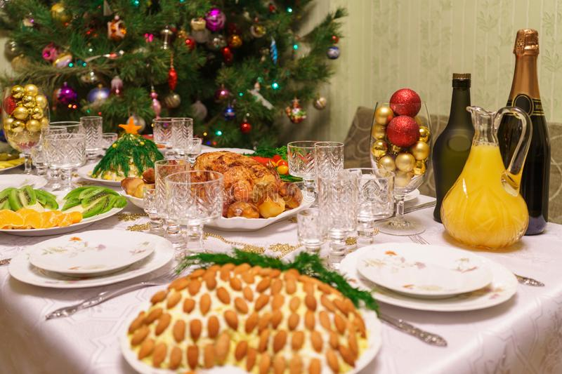 Served table with festive dishes near beautiful decorated Christmas tree in living room interior. Concept of new year holiday at royalty free stock photos