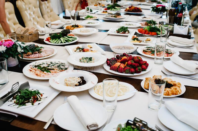 Served table with food. Plates with dishes on the table. The beginning of the holiday. Festive table in the restaurant. Side view stock photography