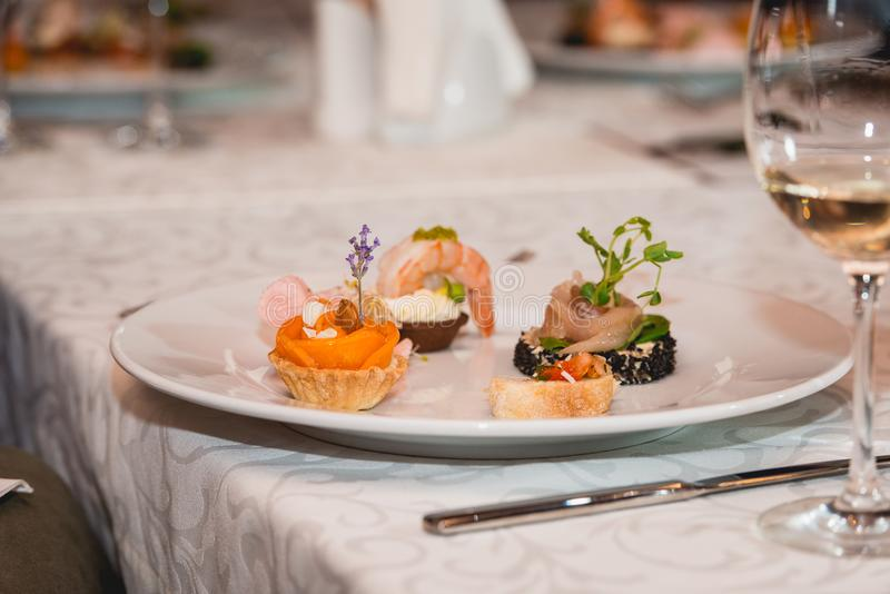 Served table for food and wine tasting. Snacks with shrimp, fish fillets, Spain tapas recipe food pintxos. Sweet snack with peach royalty free stock photos