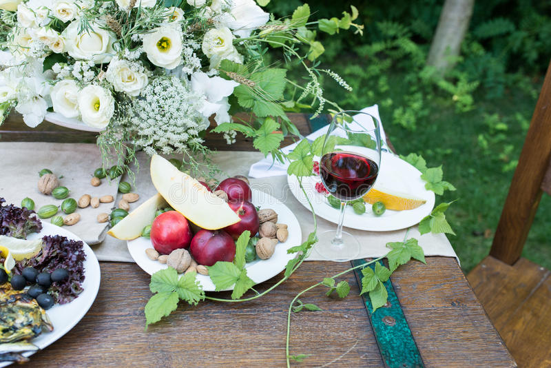 Served table with a glass of red wine, red currants, gooseberry, grilled vegetables. Outdoor served table with: a glass of red wine, melon, red currants royalty free stock image