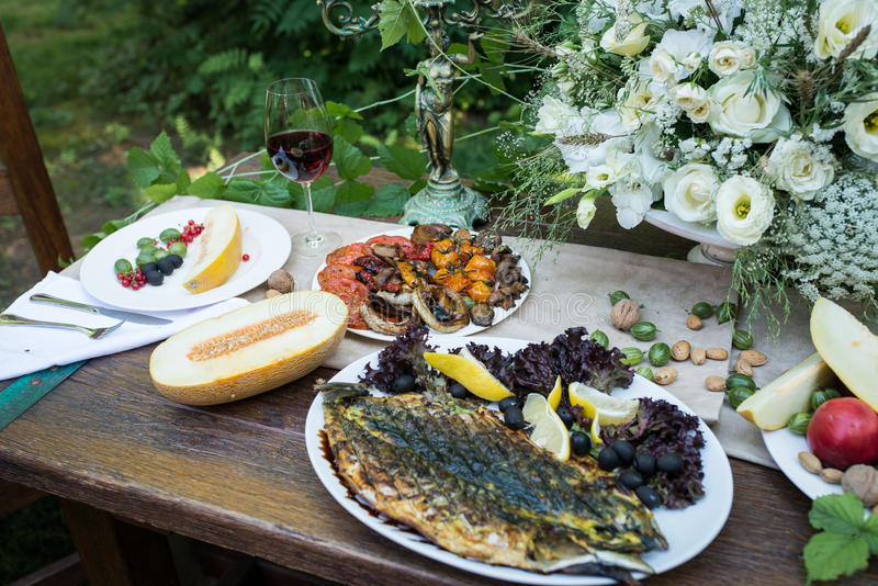Served table with grilled vegetables and fish, glass of red wine and fruits. Outdoor served table with: grilled vegetables and fish, glass of red wine, melon stock image