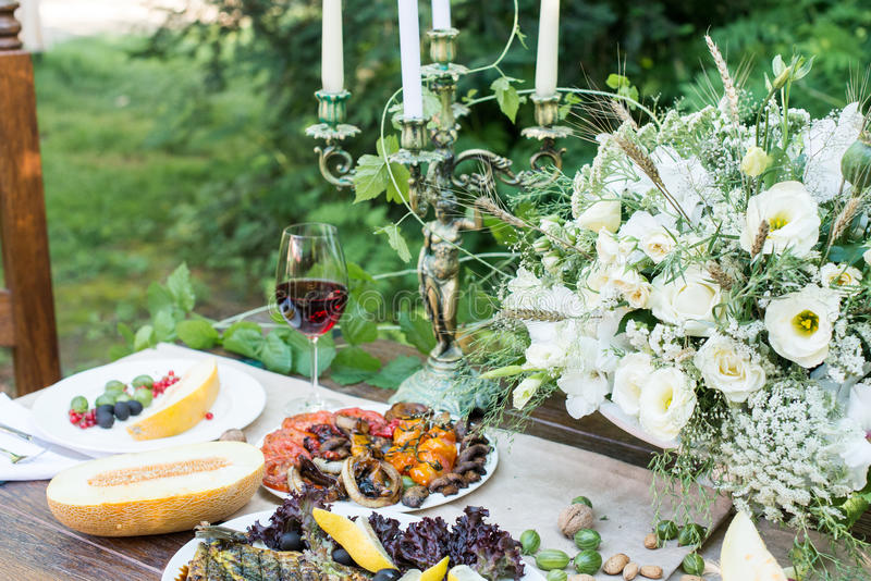 Served table with melon, grilled vegetables, glass of red wine and fruits. Outdoor served table with: melon, grilled vegetables and fish, glass of red wine, red stock photos