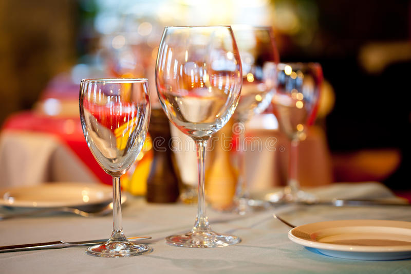 Served table in a restaurant. Romantic holiday Interior with wine glasses and crockery. Hotel service: table in a restaurant with a white tablecloth, red napkins stock photos