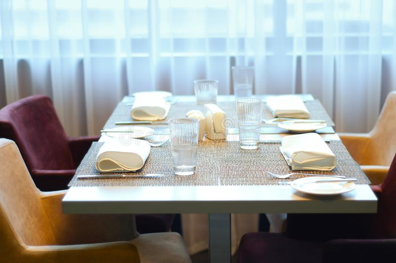 Served table and soft chairs in the cafe. Against background of windows and curtains. Served table and soft chairs in the cafe. Against the background of windows stock photo