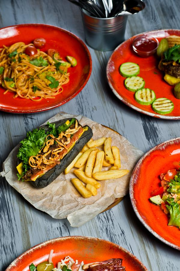 Served table with various dishes of the restaurant. Hot dog, barbecue pork ribs, steak, Carbonara paste and crab salad royalty free stock images