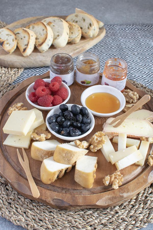 Served table - wine appetizer, cheese assortment on round wooden board, walnuts, berries, honey, jams, bread, copy space. Served table - wine appetizer, cheese stock photos