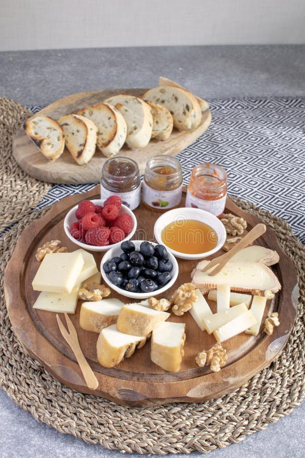 Served table - wine appetizer, cheese assortment on round wooden board, walnuts, berries, honey, jams, bread, copy space. Served table - wine appetizer, cheese stock photo