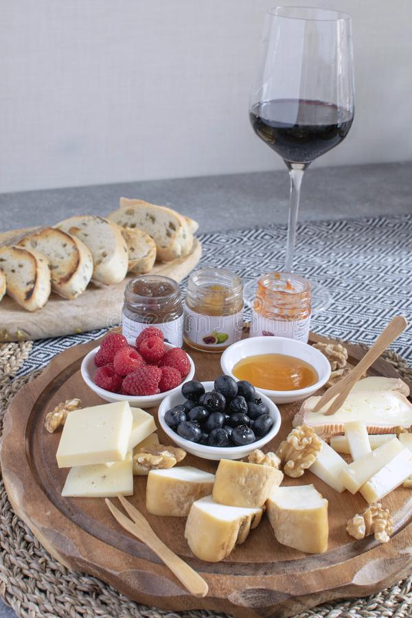 Served table - wine appetizer, cheese assortment on round wooden board, walnuts, berries, honey, jams, bread, red wine glass, copy. Space royalty free stock image