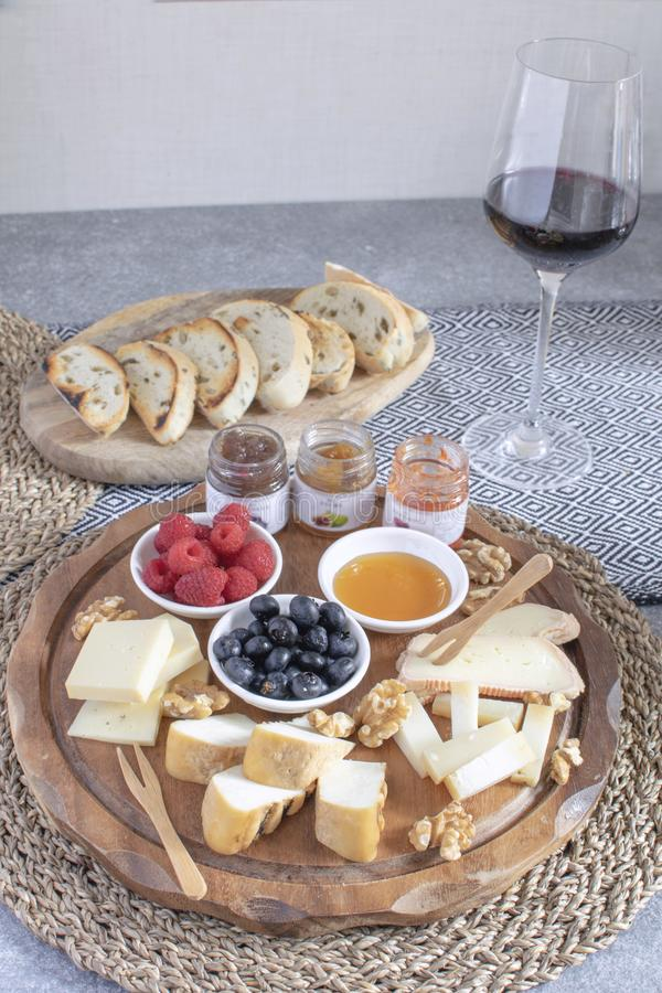 Served table - wine appetizer, cheese assortment on round wooden board, walnuts, berries, honey, jams, bread, red wine glass, copy. Space stock image