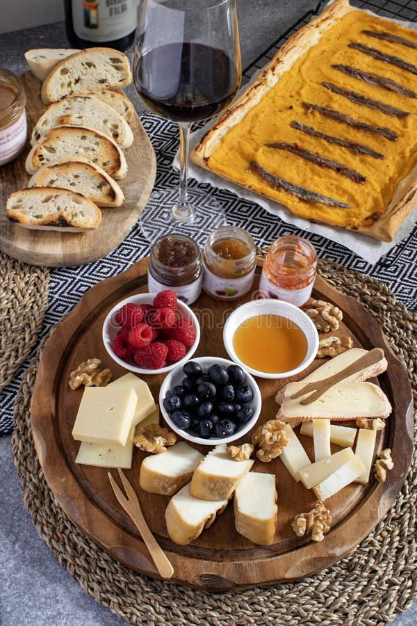Served table - wine appetizer, cheese assortment on round wooden board, walnuts, berries, honey, jams, bread, red wine, savory. Pumpkin pie with anchovies, copy stock images