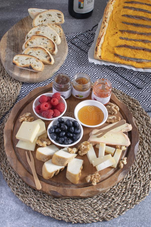 Served table - wine appetizer, cheese assortment on round wooden board, walnuts, berries, honey, jams, bread, red wine, savory. Pumpkin pie with anchovies, copy stock image