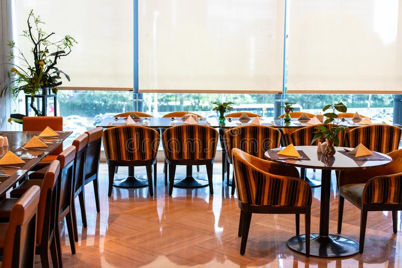 Served tables in the hotel restaurant. The banquet room is ready to receive guests. Roller blinds omitted and a Chinese. Served tables in the restaurant. Tables stock photo