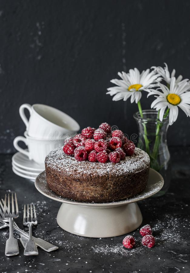 Served tea table still life - chocolate nut cake with raspberry on a dark background. Delicious dessert.Flat lay royalty free stock image