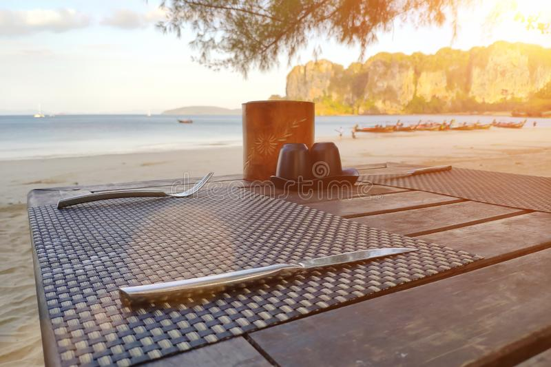 Served wooden table on a tropical beach. Prepared for breakfast near the sea stock photos