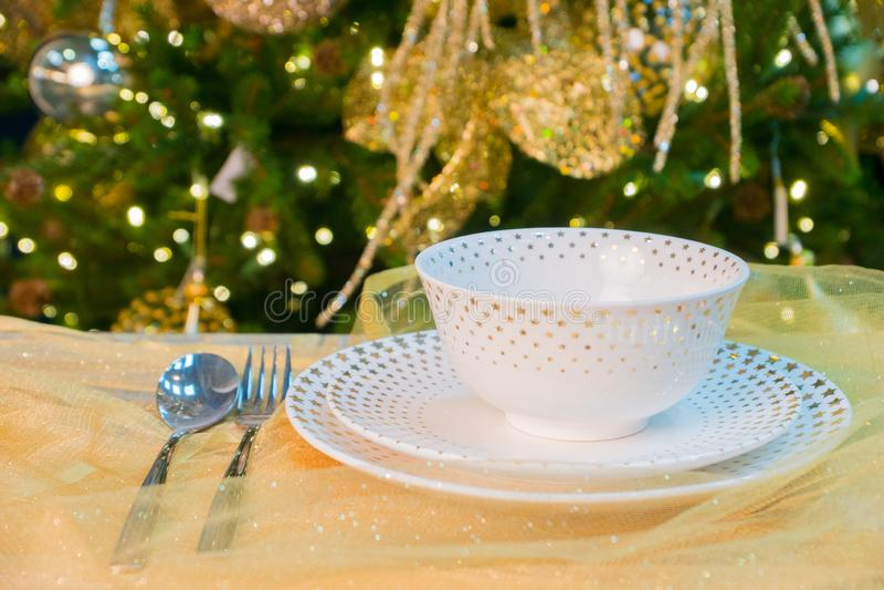 Served xmas table near decorated evergreen tree royalty free stock photos