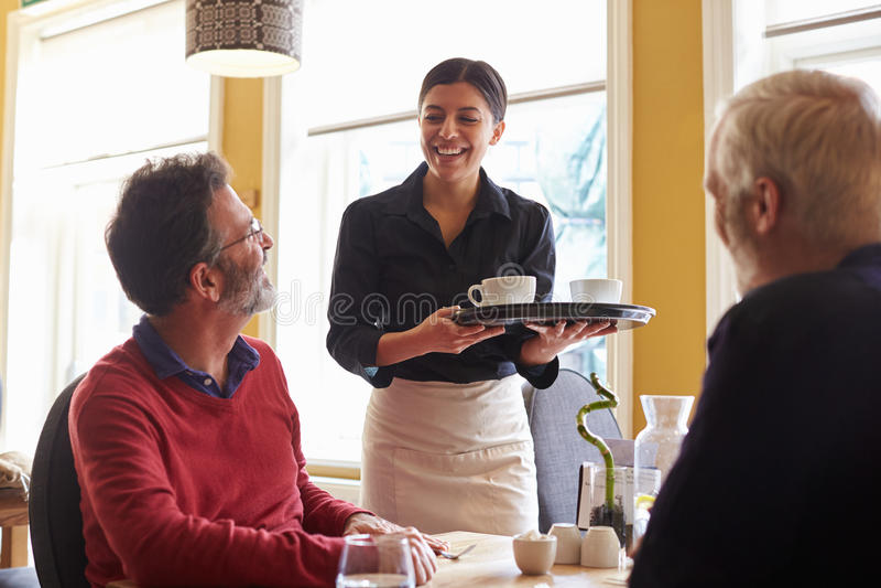 Serveerster brengende koffie aan een mannelijk paar bij een restaurant stock fotografie