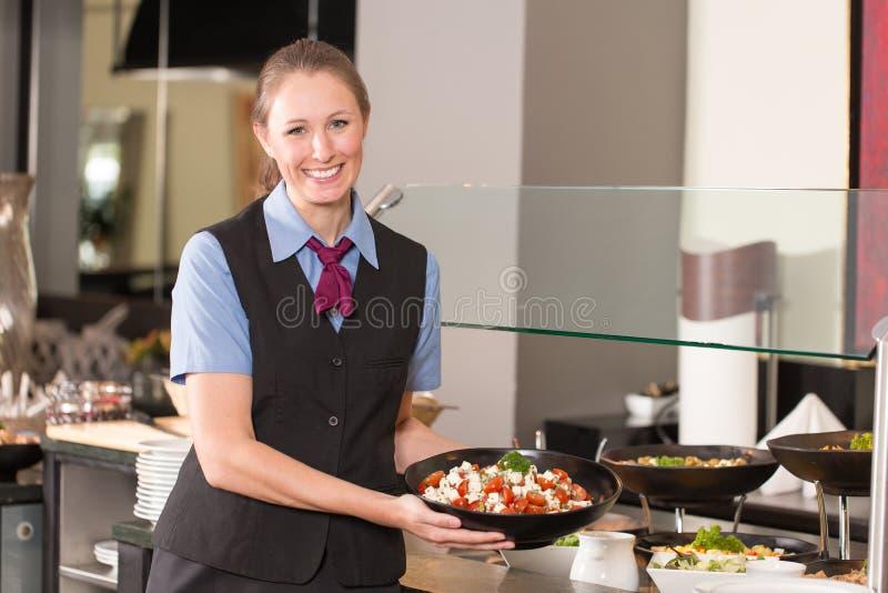 Serveerster of cateringsberoeps die voedsel zetten in buffet royalty-vrije stock foto
