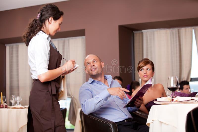Serveerster die de orde van restaurantlijst neemt stock fotografie
