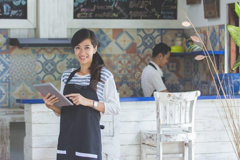 Serveerster die digitale tablet in koffie gebruiken stock foto