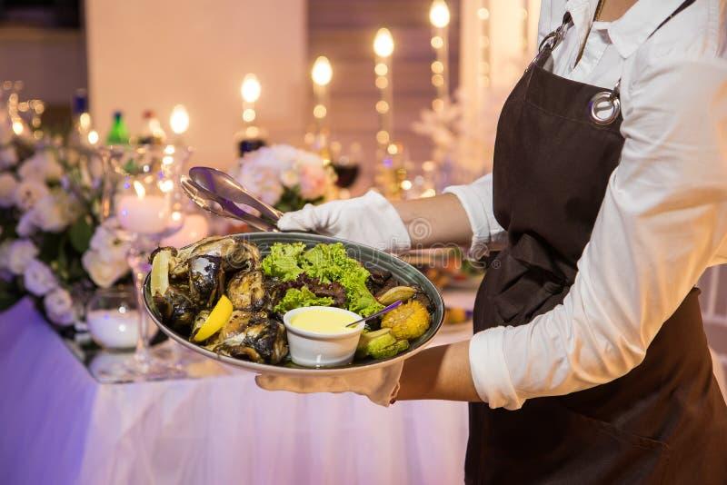 Serveerster die een schotel met zeevruchten en groenten houden stock foto