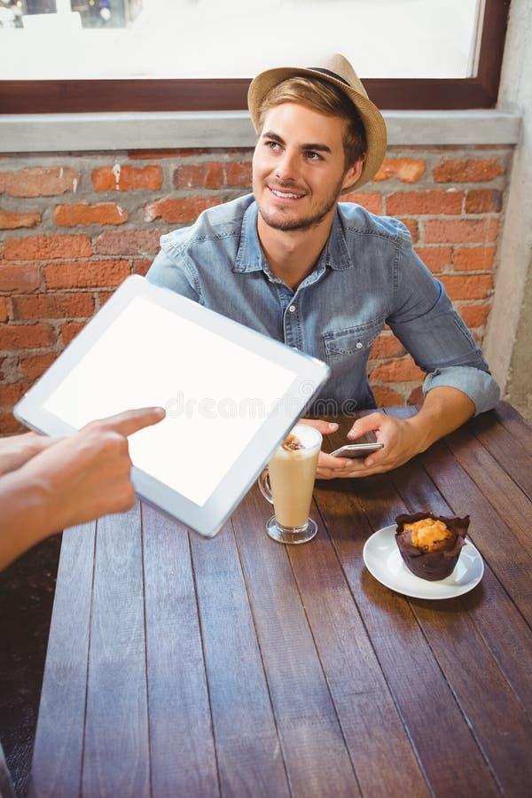 Serveerster die knappe hipstersorde met tablet nemen royalty-vrije stock foto's