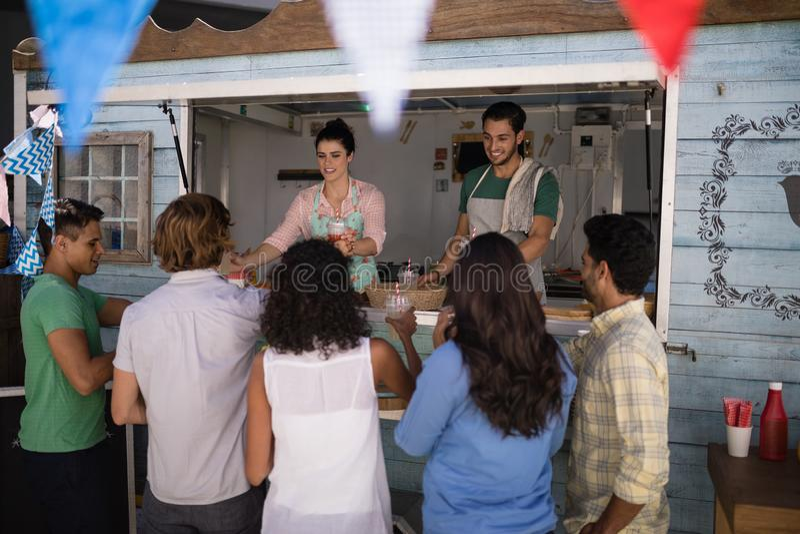 Serveerster die sap geven aan klant bij teller stock foto
