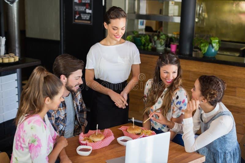 Serveerster die zich door klanten in restaurant bevinden royalty-vrije stock afbeelding