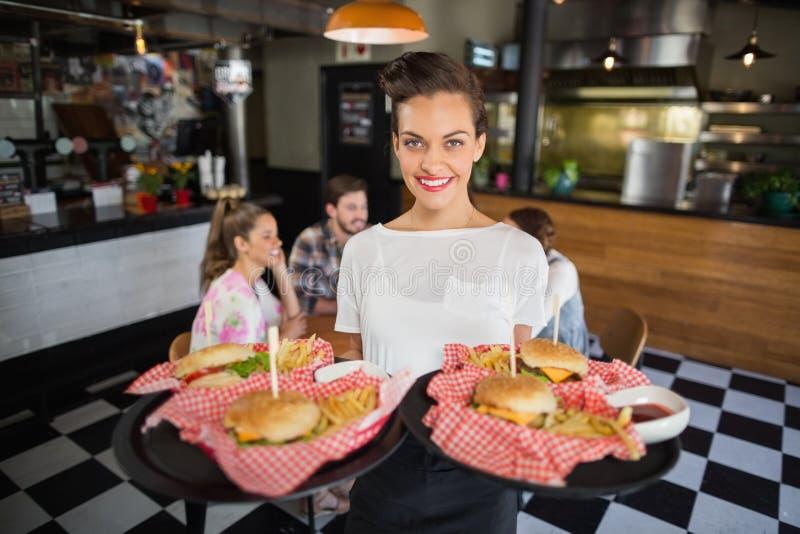 Serveerster dienende hamburger terwijl klanten die in restaurant zitten royalty-vrije stock foto's