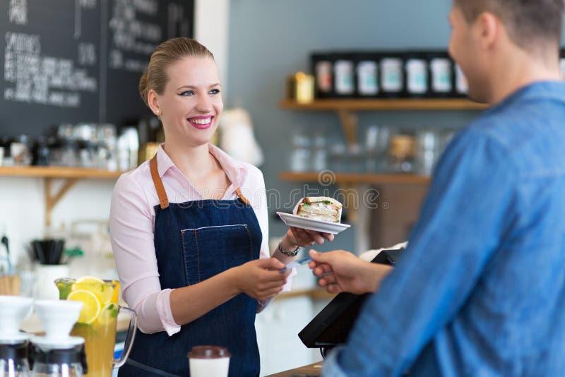Serveerster dienende klant bij de koffiewinkel royalty-vrije stock foto