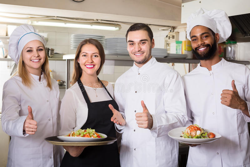 Serveerster en bemanning van professionele koks die bij restaurant stellen royalty-vrije stock foto