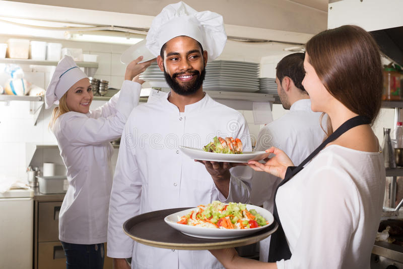 Serveerster en bemanning van professionele koks die bij restaurant stellen royalty-vrije stock foto's