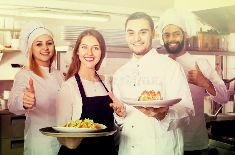 Serveerster en bemanning van professionele koks die bij restaurant stellen royalty-vrije stock afbeeldingen