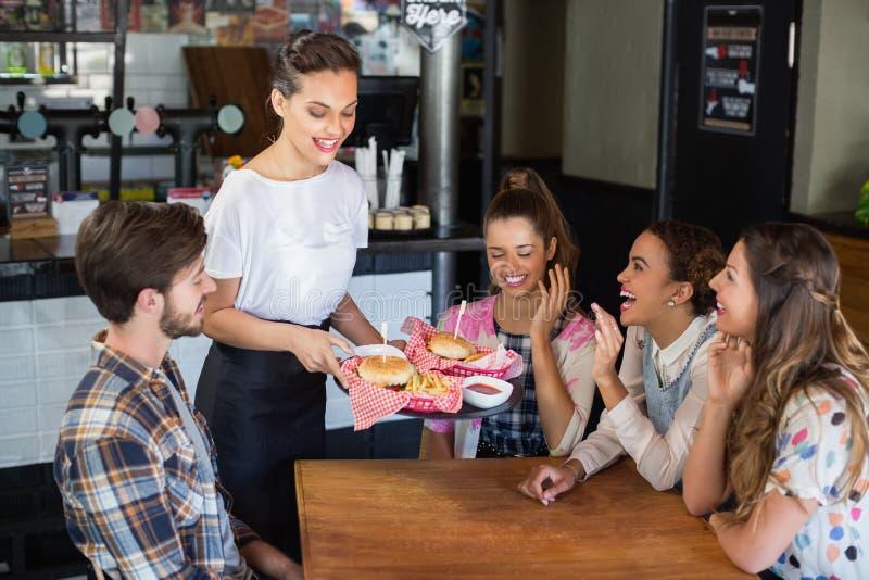 Serveerster het dienen burgers aan klanten in restaurant royalty-vrije stock afbeeldingen