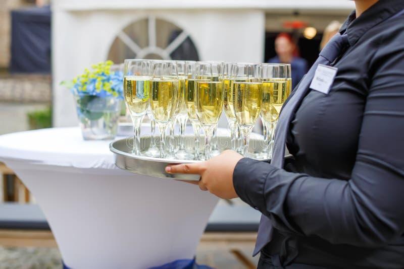Serveerster met schotel van champagne en wijnglazen royalty-vrije stock afbeeldingen