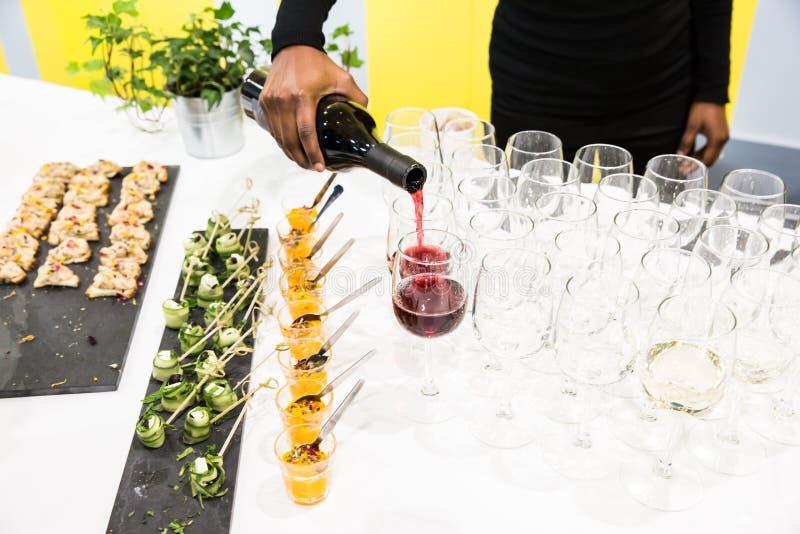 Serveerster Pouring Red Wine in Glazen bij Buffetlijst met Wit royalty-vrije stock fotografie