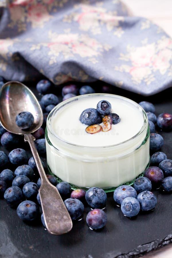 Servendo del yogurt con gli interi mirtilli e farina d'avena freschi sulla vecchia Tabella rustica immagine stock libera da diritti