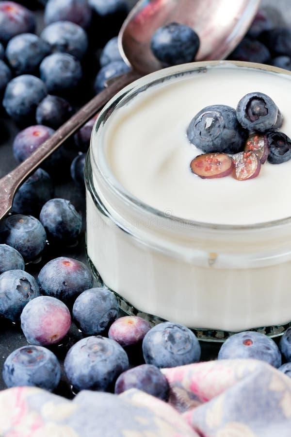 Servendo del yogurt con gli interi mirtilli e farina d'avena freschi sulla vecchia Tabella rustica immagini stock libere da diritti