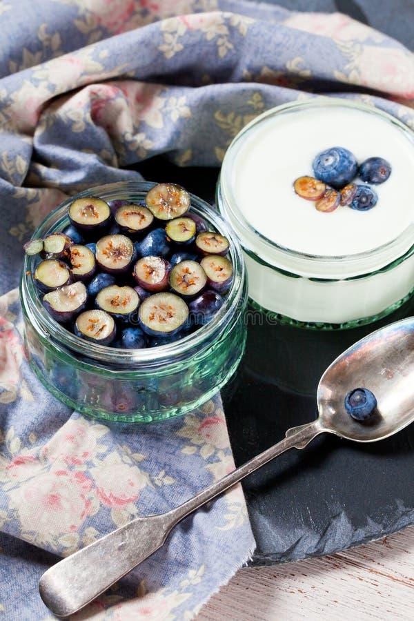 Servendo del yogurt con gli interi mirtilli e farina d'avena freschi sulla vecchia Tabella rustica fotografia stock