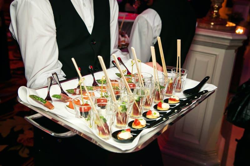 Server che tiene un vassoio di aperitivi al banchetto immagini stock