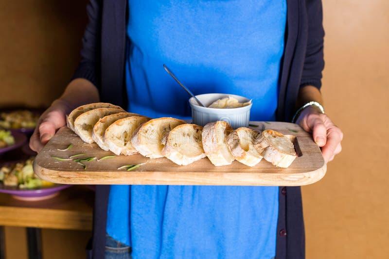 Server che tiene vassoio di legno con pane di recente al forno e burro casalingo Le mani delle donne con il server di legno degli fotografie stock