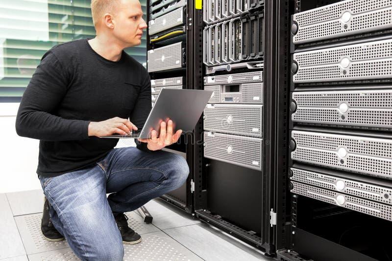 Server di With Laptop Monitoring del consulente in centro dati immagini stock