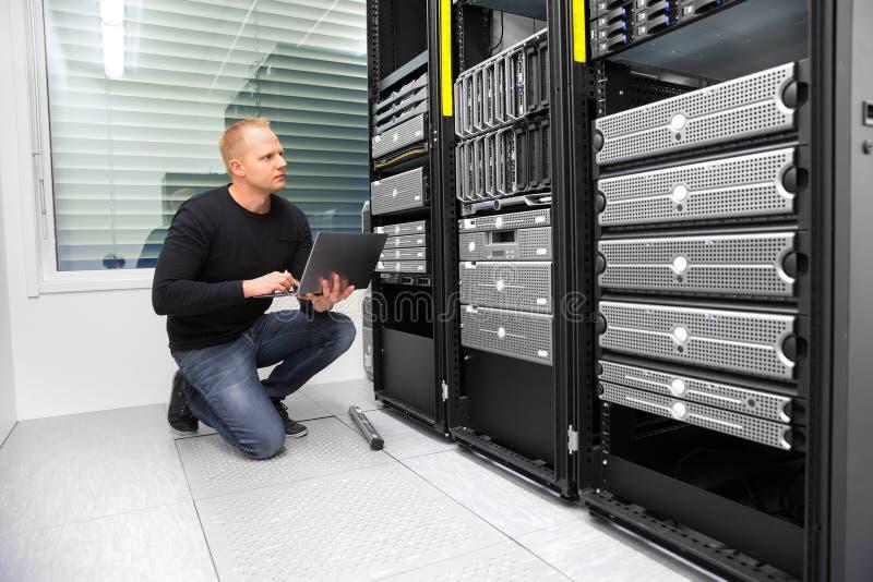 Server di monitoraggio di Using Laptop While del consulente in centro dati fotografia stock