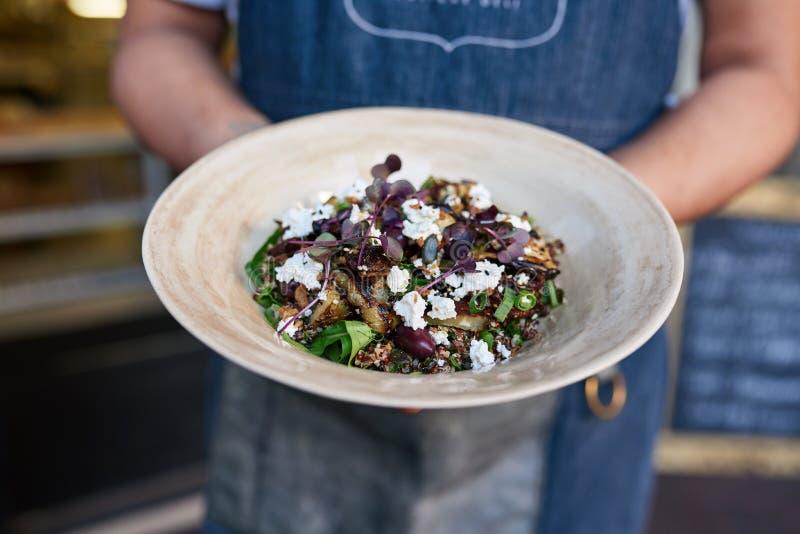 Server die een heerlijke saladeplaat houden bij een bistro royalty-vrije stock foto's