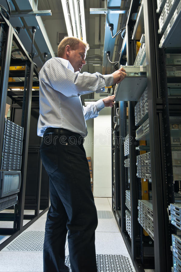 Server Expansion. IT administrator installing a new rack mount server. Large scale storage server is also seen royalty free stock photos