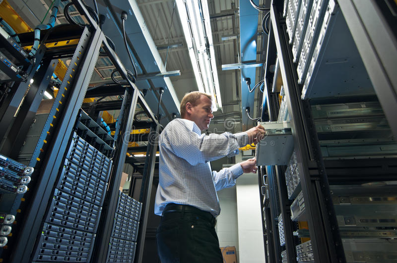Server Expansion. IT administrator installing a new rack mount server. Large scale storage server is also seen stock images