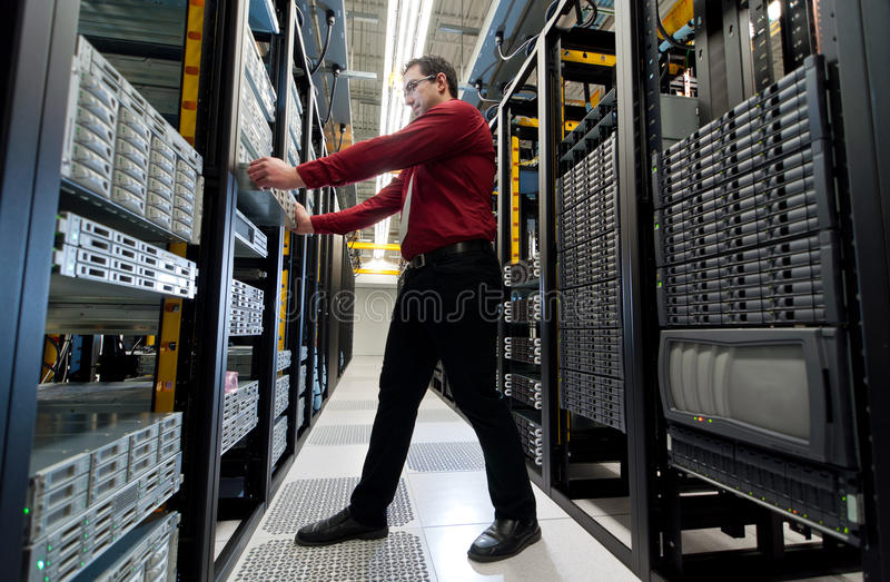 Server Expansion. IT administrator installing a new rack mount server. Large scale storage server is also seen