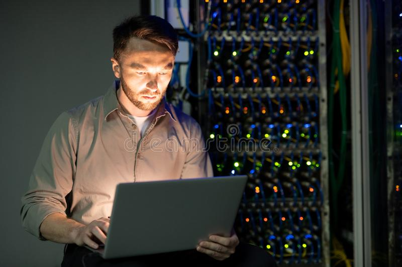 Server manager in data center. Concentrated young bearded server manager in shirt working with laptop in dark room of data center stock photo