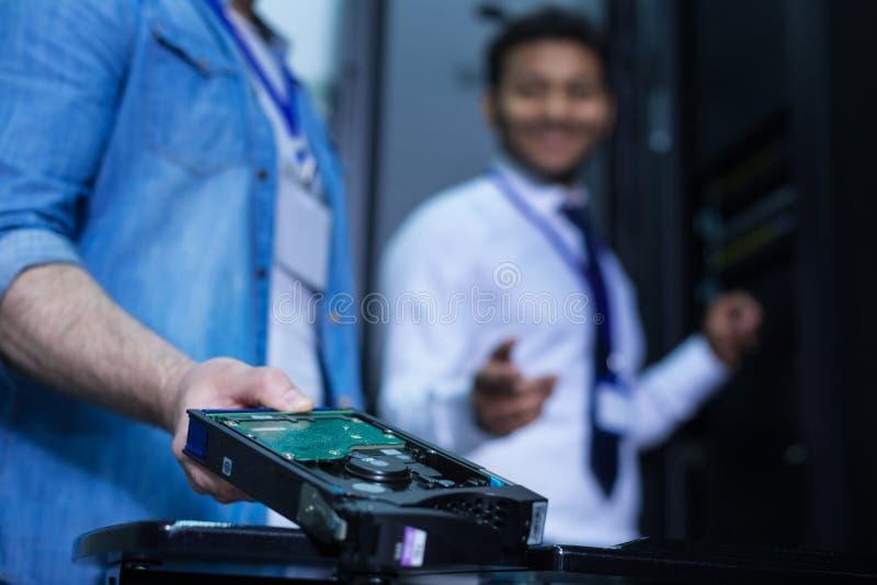 Server moderno dello scaffale che è tenuto da un tecnico professionista immagine stock