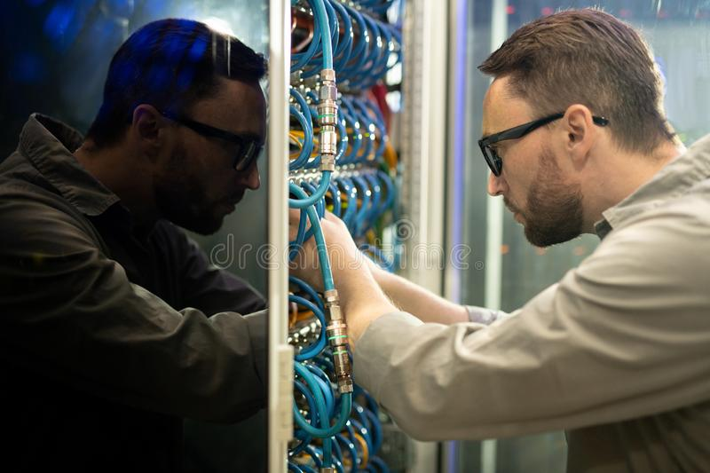 Server repairman connecting cables to supercomputer. Side view of concentrated young server repairman in glasses standing in server room and connecting cables to royalty free stock photos